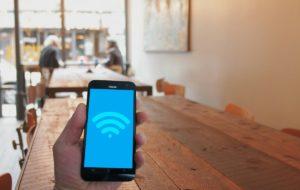Wifi point chaud public Voyage concept l'Internet accès Entreprise café ville fermer la communication relier connexion Cyber la cyber-sécurité cybersecurity Les données dispositif numérique main en portant icône mobile téléphone appareil électronique La technologie gadget table sol sol meubles